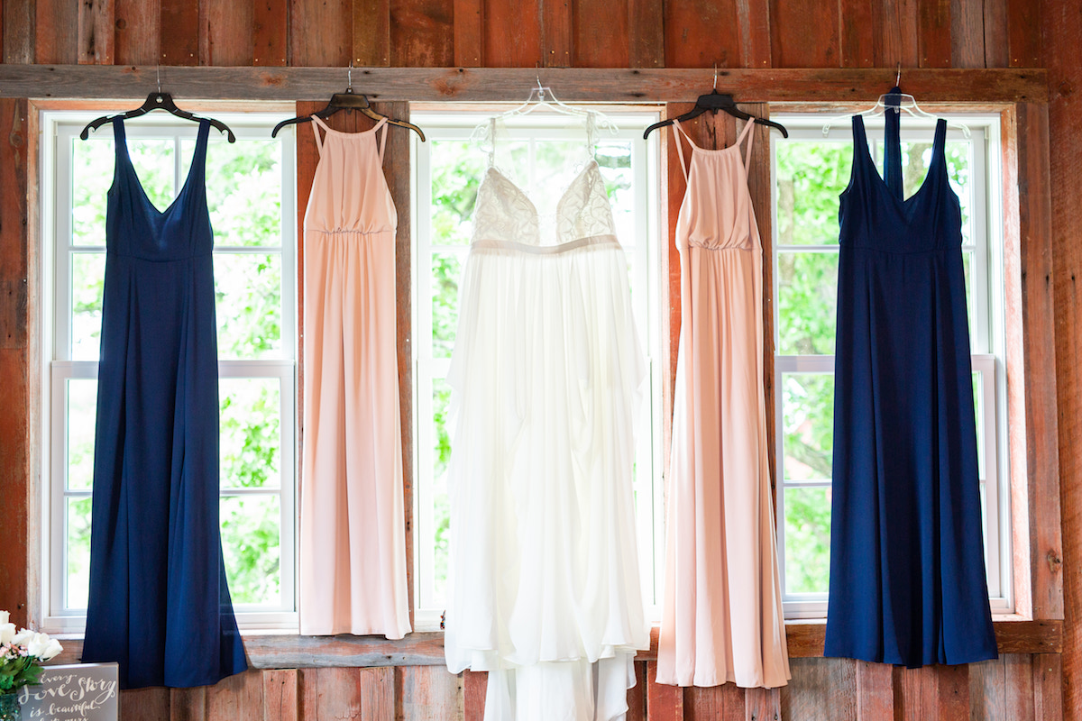 bridal_wedding_gown_hanging_next_to_pink_and_navy_briesmaid_dresses.jpg