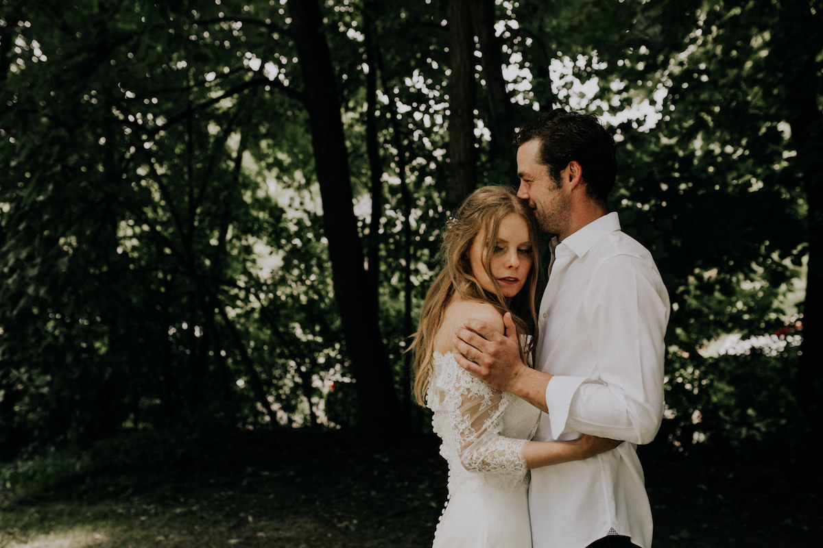 bride_and-groom_embracing_in_green_forrest_backyard.jpg