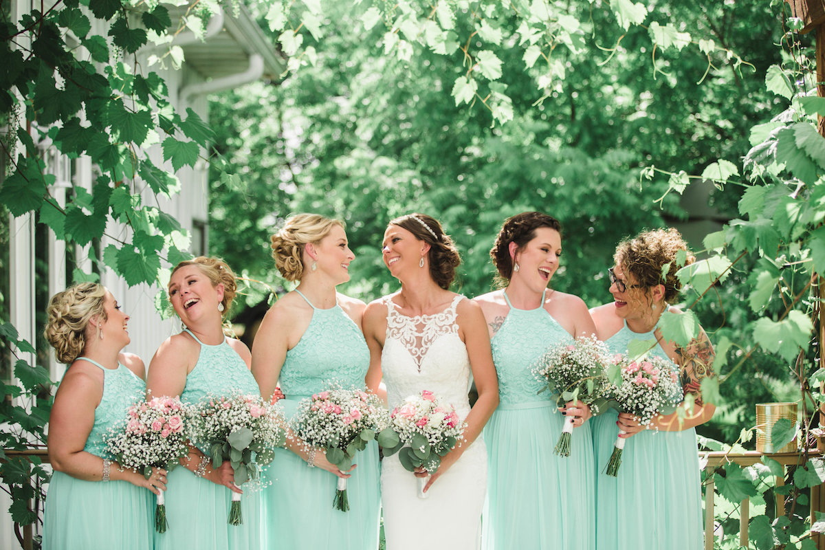 bride_and_bridesmaids_in_tealdresses_surrounded_by_green_leaves_outdoors.jpg