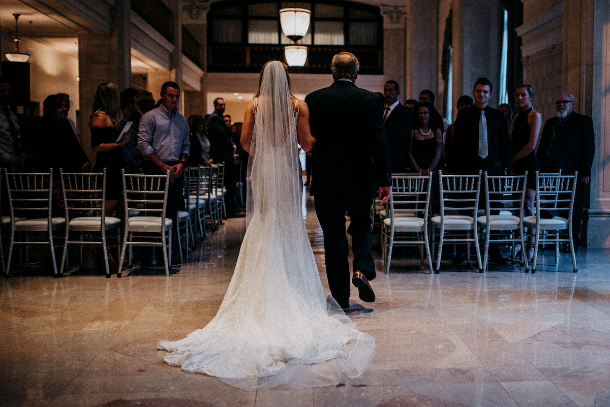 bride_and_father_walking_down_wedding_aisle_marble_floor.jpg