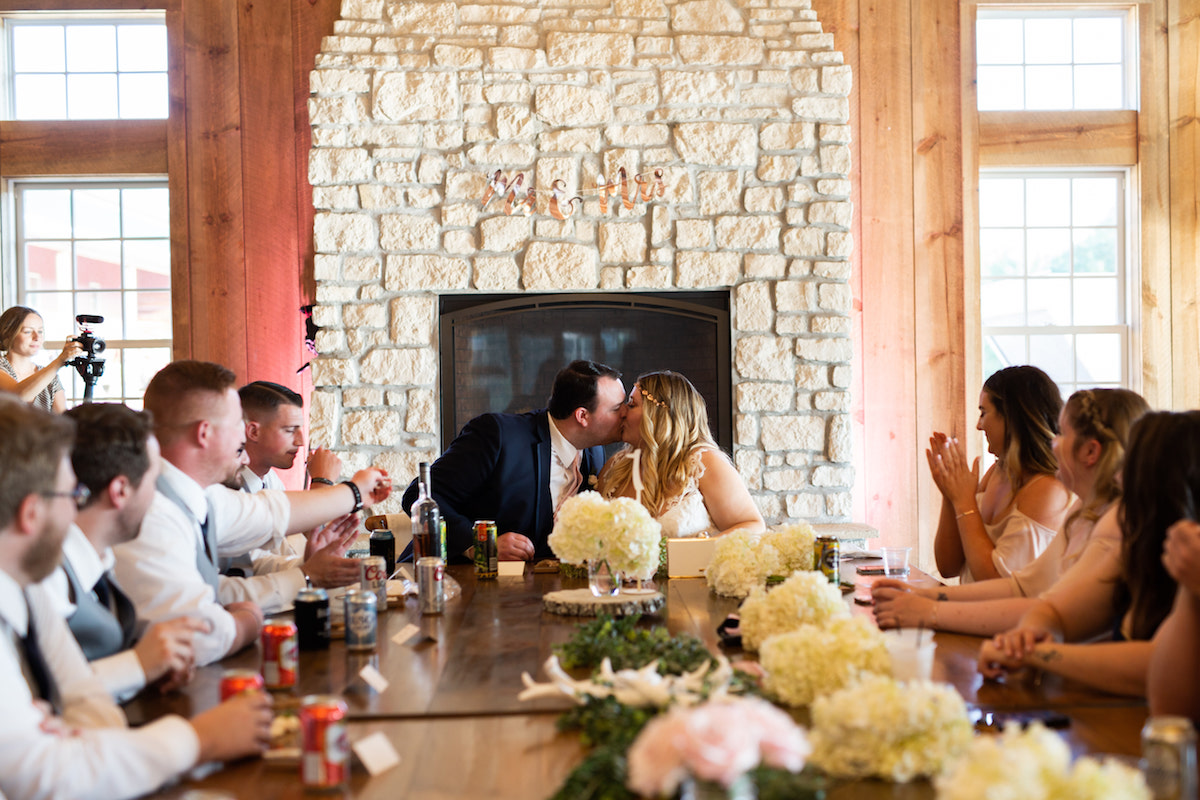 bride_and_groom_at_head_of_wedding_table_brick_fireplace_behind_in_cozy_wooden_wall_venue.jpg