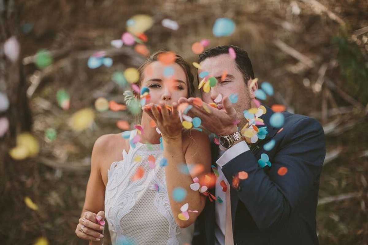 bride_and_groom_blow_confetti.jpg