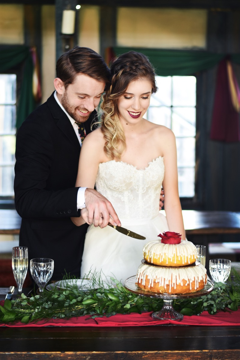 bride_and_groom_cutting_bundt_weddig_cake_renassiance_fair.jpg