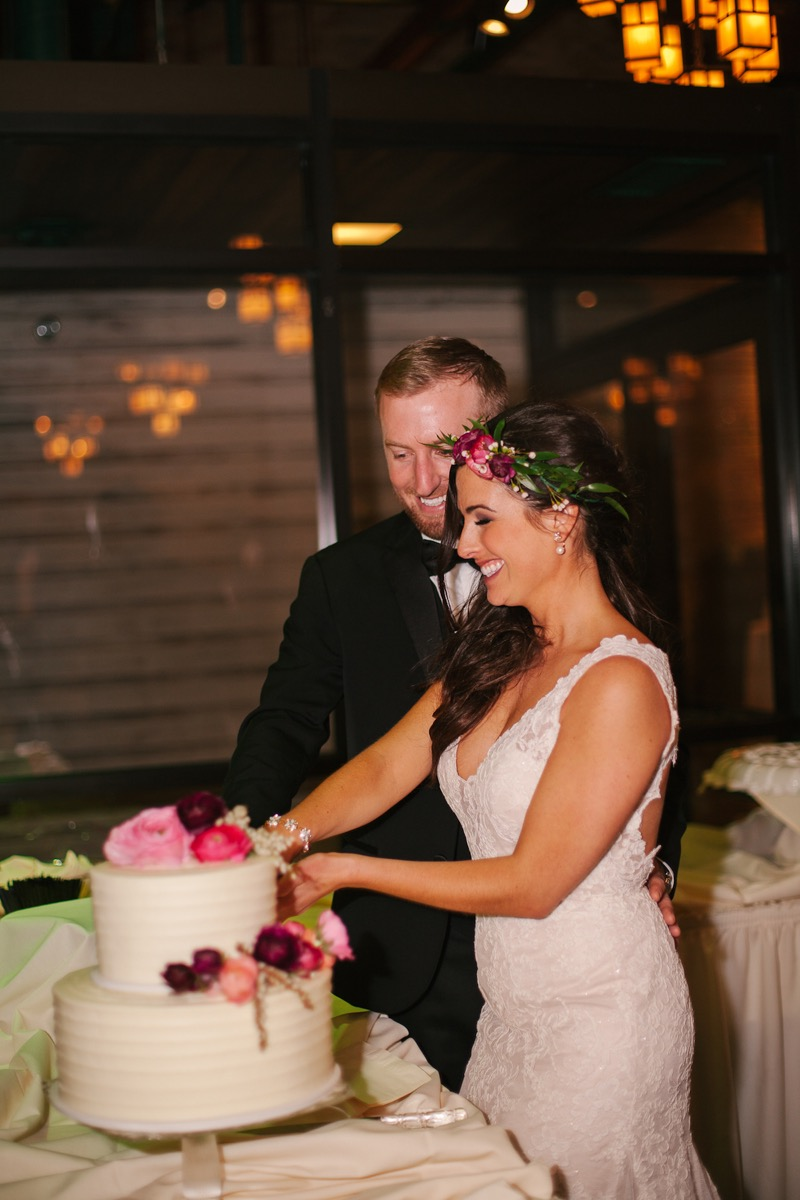 bride_and_groom_cutting_white_cake_pink_red_flowers.jpg