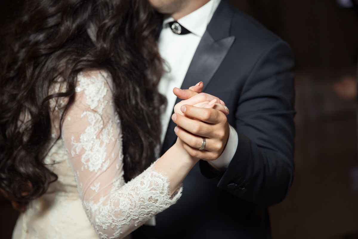 bride_and_groom_dancing_together_navy_tux_lace_gown.jpg