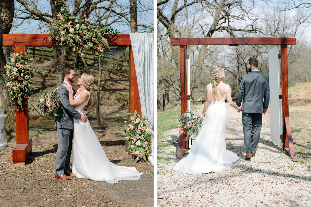 bride_and_groom_embrace_in_front_of_wooden_arch_with_floral_decor_walking_holding_hands.jpg
