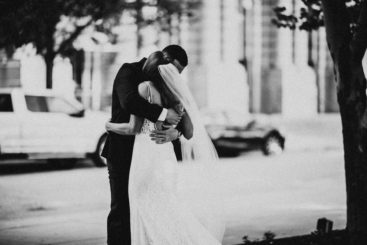 bride_and_groom_embrace_in_park_black_and_white.jpg