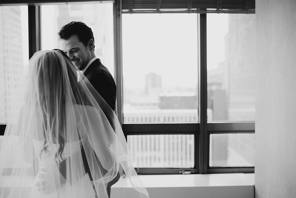 bride_and_groom_embracing_by_city_skyline_windows_black_and_white.jpg