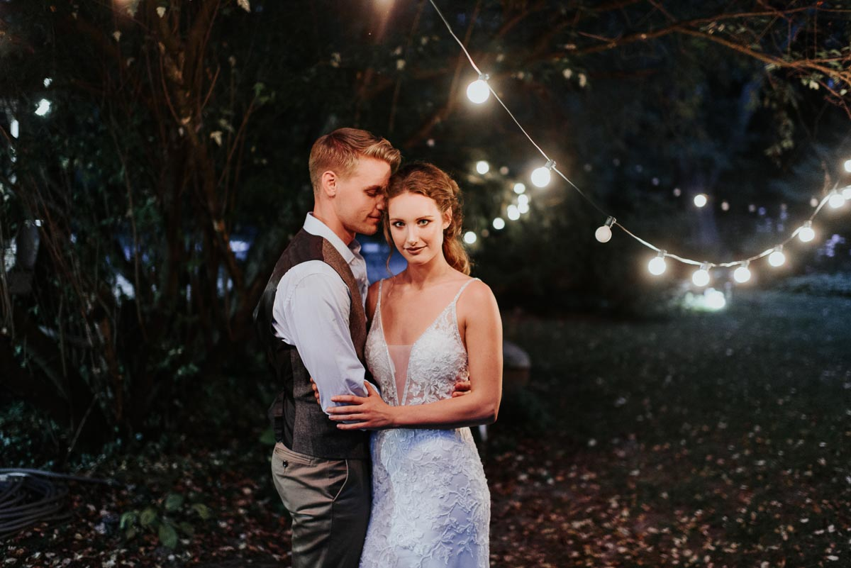 bride_and_groom_embracing_by_string_lights.JPG
