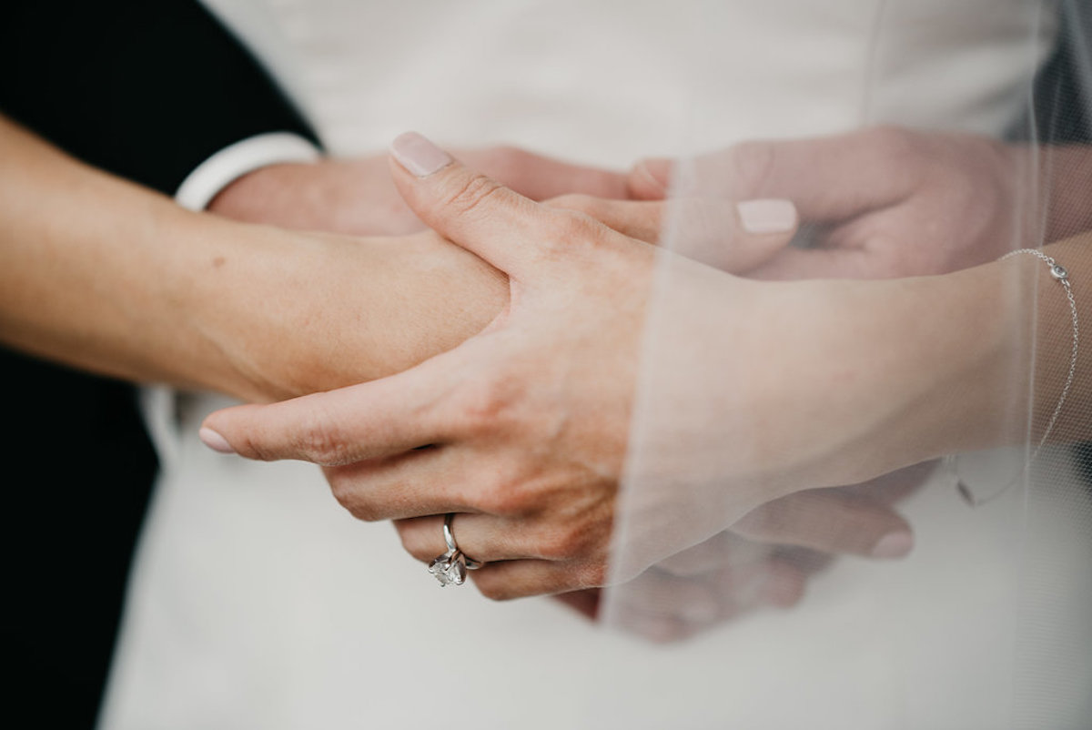 bride_and_groom_embracing_holding_hands_diamond_wedding_ring.jpg