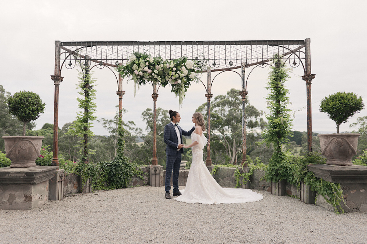 bride_and_groom_embracing_in_french_courtyeard_with_greenery.jpg