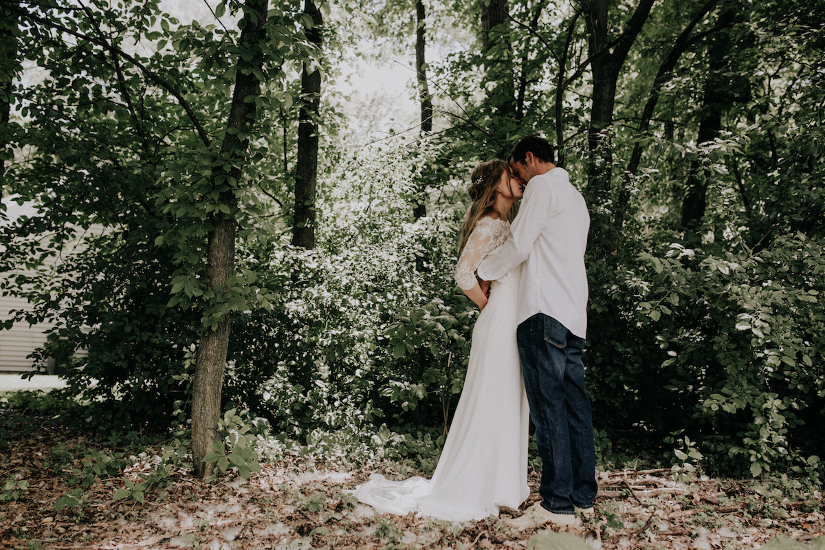 bride_and_groom_embracing_intimate_backyard_trees_leaves.jpg