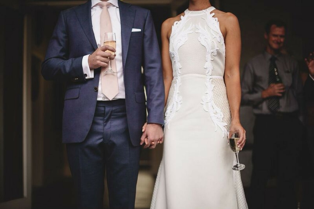 bride_and_groom_hold_hands_with_wine.jpg
