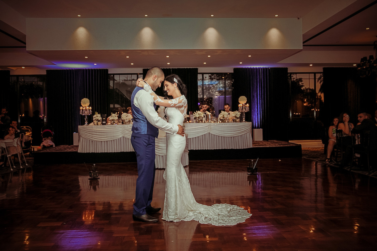 bride_and_groom_holding_each_other_during_first_dance_smiling_glamorous_reception_venue.jpg