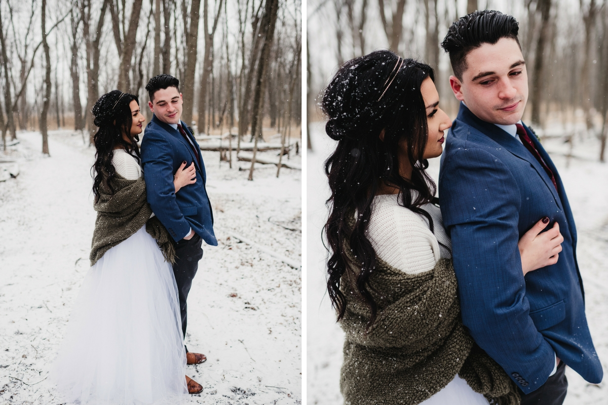 bride_and_groom_holding_each_other_on_winter_woods_snowy_path.jpg