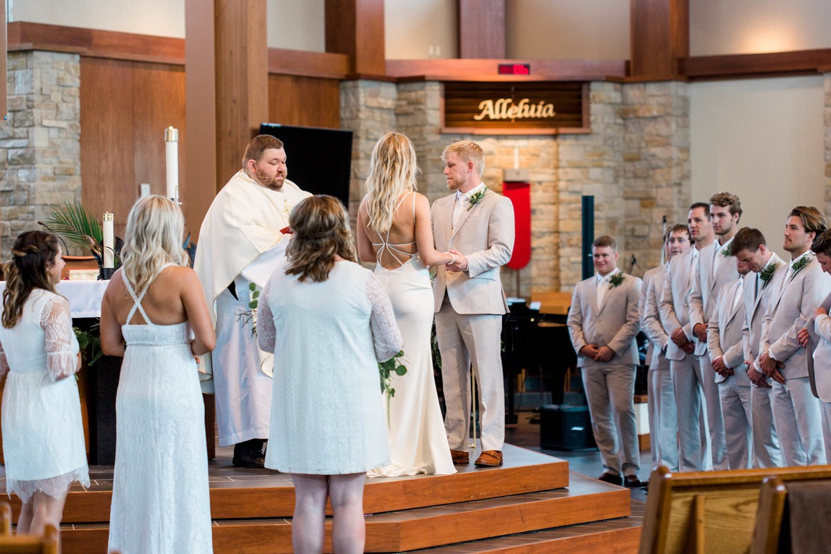bride_and_groom_holding_hands_at_indoor_church_altar.jpg
