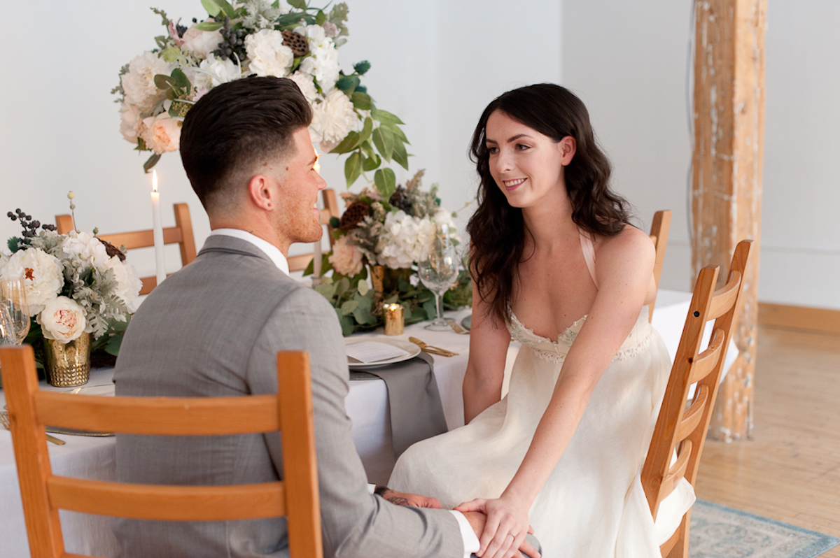 bride_and_groom_holding_hands_at_table.jpg