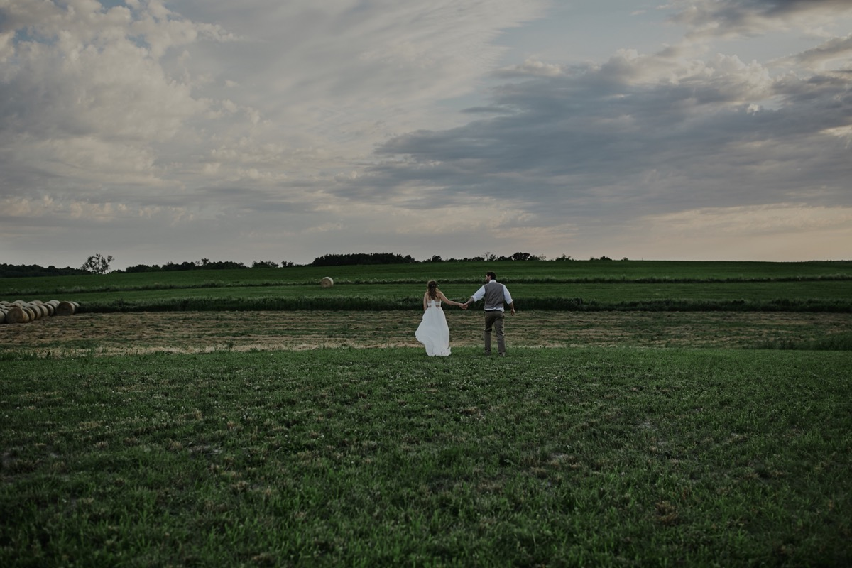 bride_and_groom_holding_hands_standing_apart_field.JPG