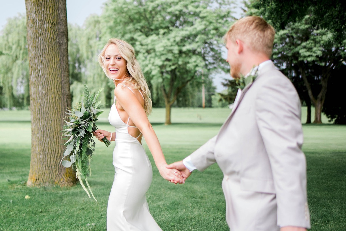 bride_and_groom_holding_hands_walking_at_country_club.jpg
