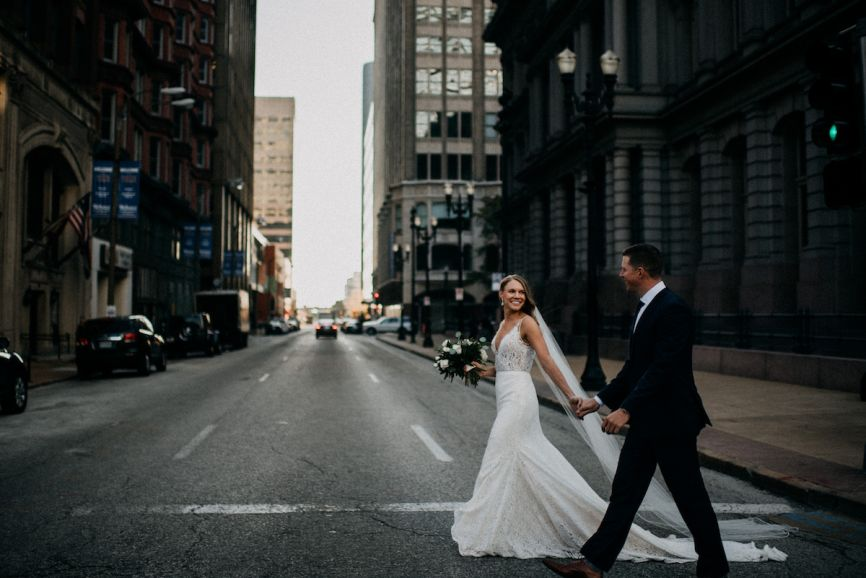 bride_and_groom_holding_hands_walking_in_downtown_city_street_smiling.jpg