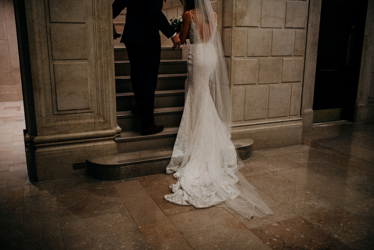 bride_and_groom_holding_hands_walking_up_stone_staircase.jpg