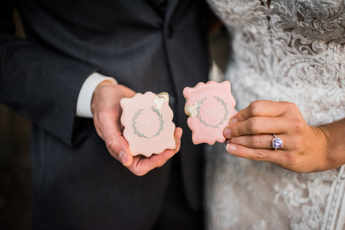 bride_and_groom_holding_pink_greenery_wedding_cookies.jpg