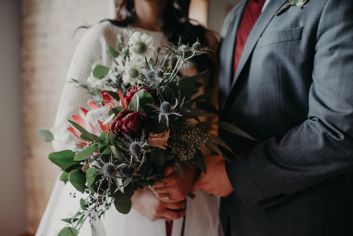 bride_and_groom_in_ceremony_with_large_bouquet.jpg