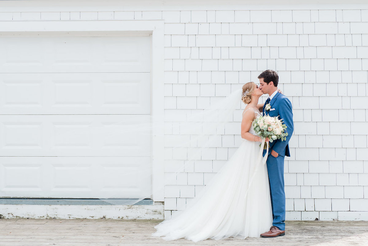 bride_and_groom_in_navy_suit_kiss_in_front_of_white_building.jpg