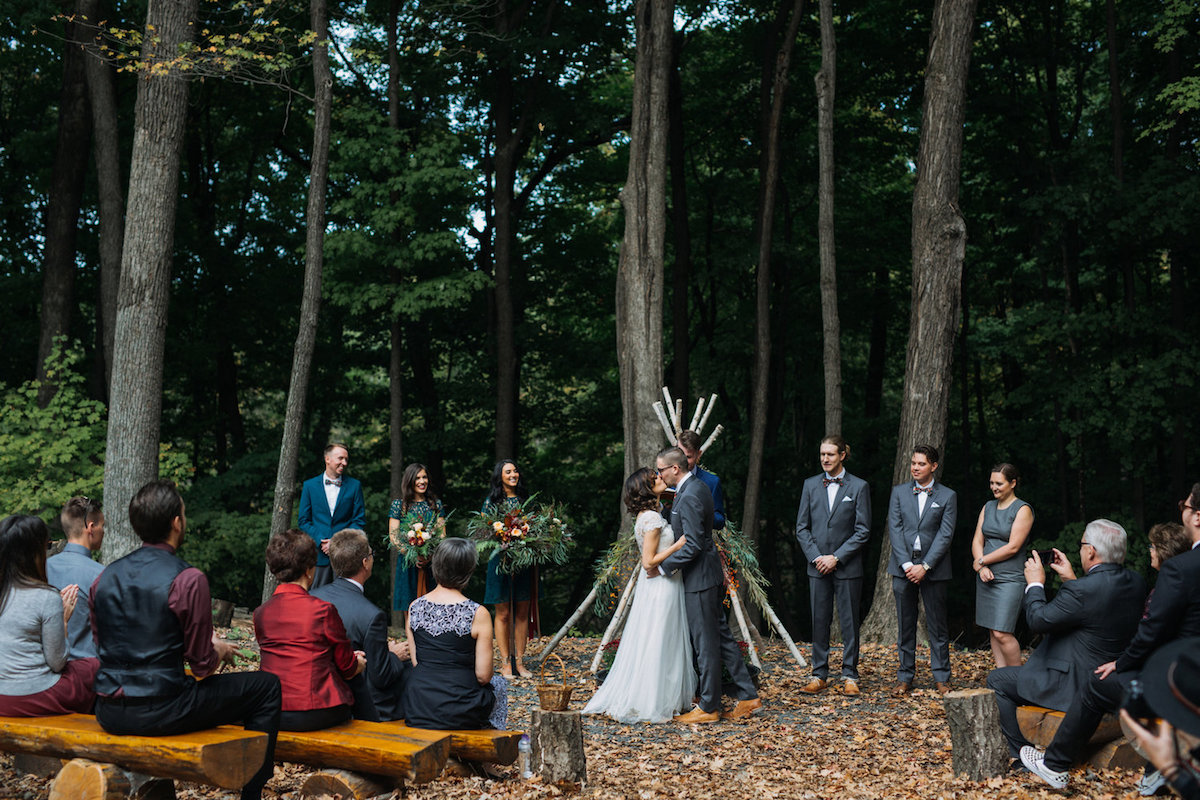 bride_and_groom_kiss_during_camp_wedding_in_woods.jpg