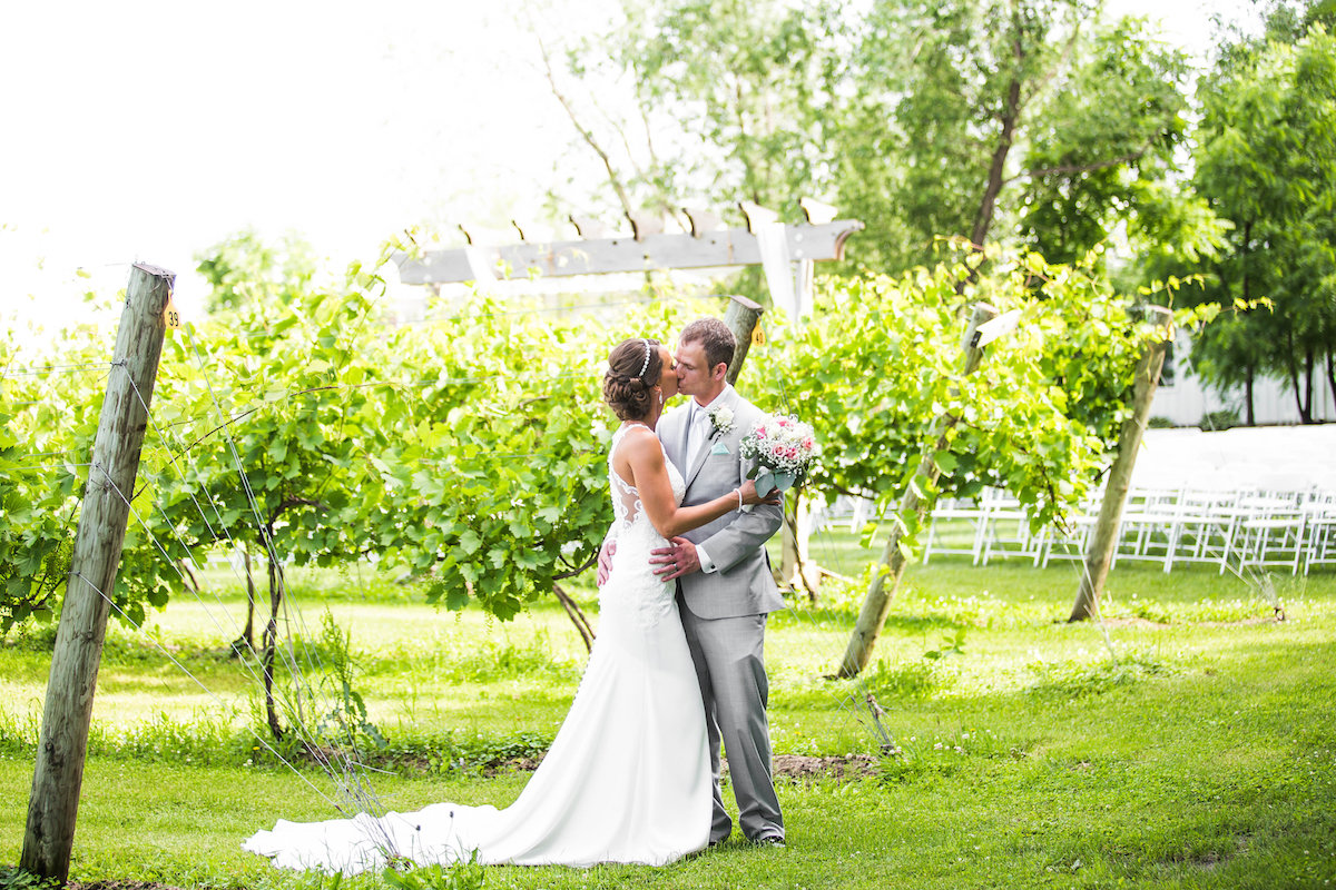 bride_and_groom_kiss_on_winery_bright_green_trees_grass.jpg