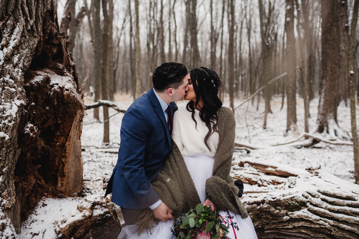 bride_and_groom_kissing_in_moody_winter_forest.jpg