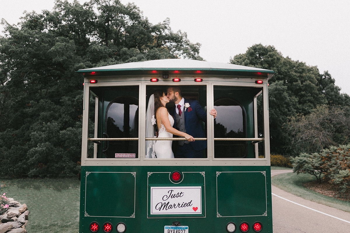 bride_and_groom_kissing_on_just_married_trolley_mn.jpg
