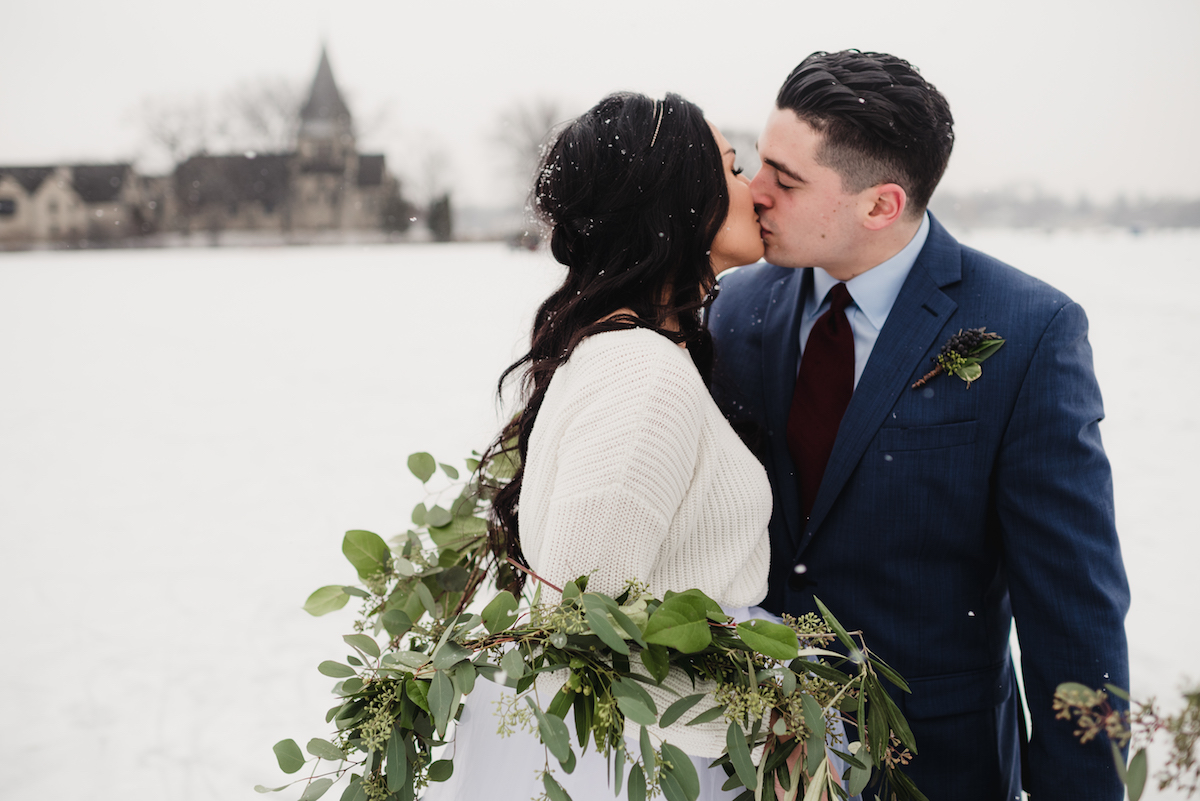 bride_and_groom_kissing_with_green_leaves_snowy_day.jpg