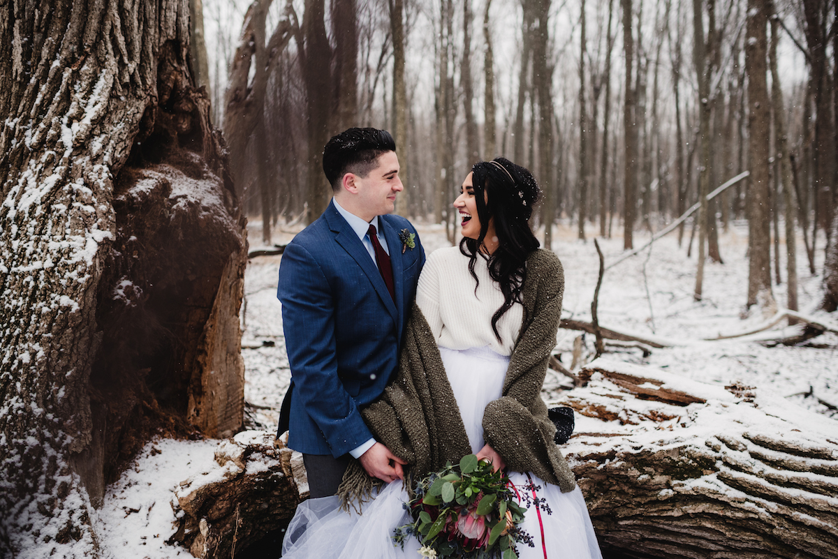bride_and_groom_laughing_in_snowy_moody_forest.jpg