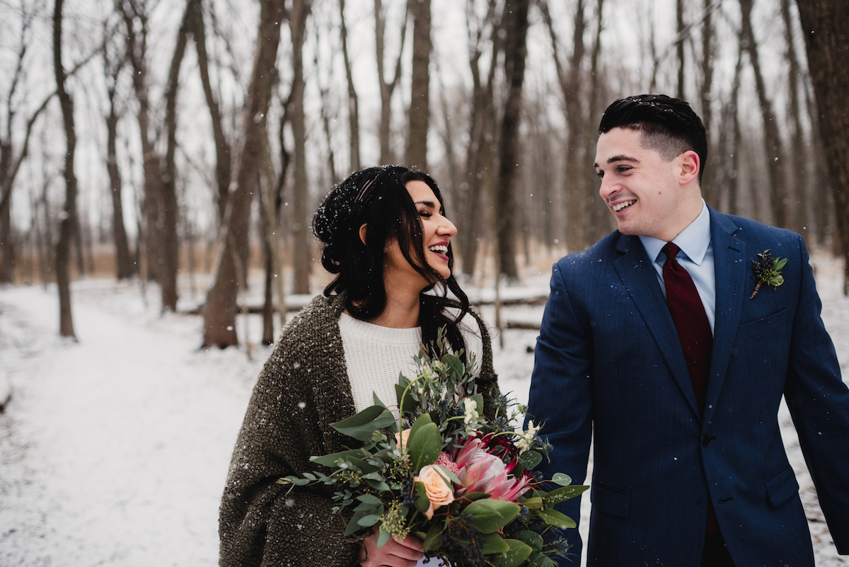 bride_and_groom_laughing_on_snowy_forest_path.jpg
