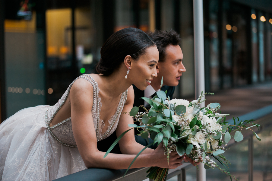bride_and_groom_leaning_against_railing_looking_out.jpg