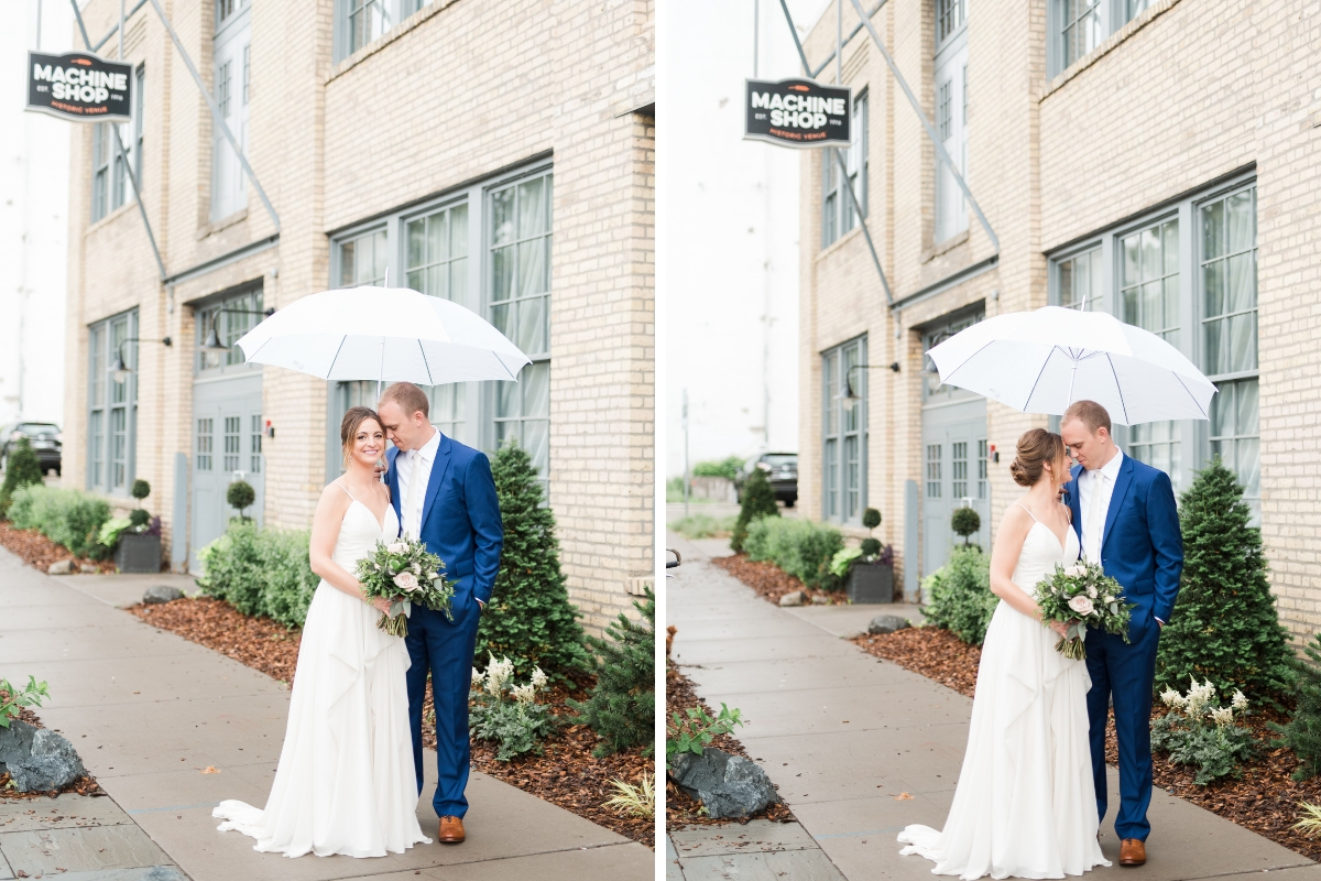 bride_and_groom_ouside_industrial_wedding_venue_under_white_umbrella_groom_in_navy_suit.jpg