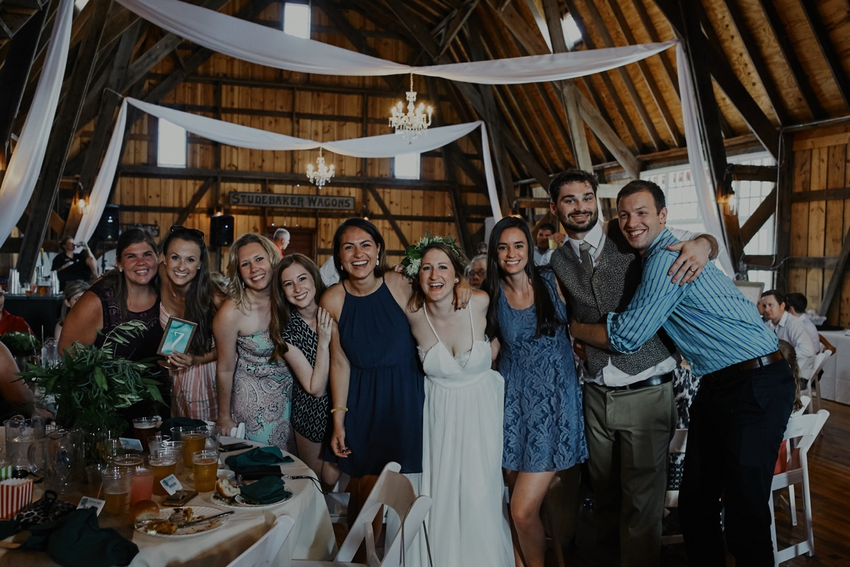 bride_and_groom_posing_with_wedding_guests_barn.JPG