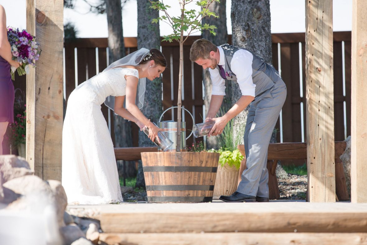 bride_and_groom_pouring_sand_into_bin_wedding_ceremony.jpg