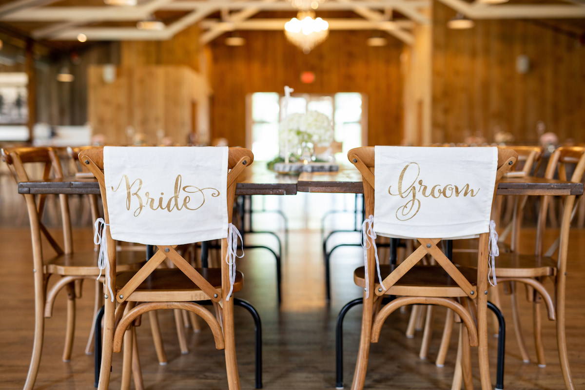 bride_and_groom_seat_coverings_in_wooden_venue_dinner_table.jpg
