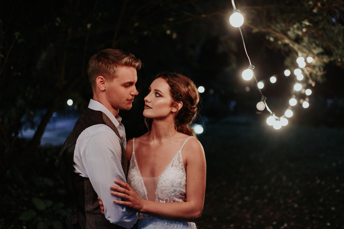 bride_and_groom_share_a_look_twinkling_lights.JPG