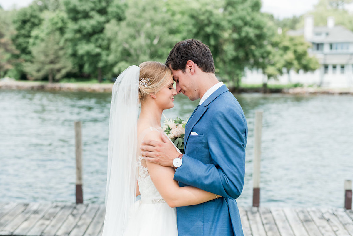 bride_and_groom_share_close_moment_on_lake_dock.jpg