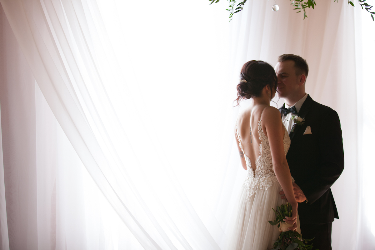 bride_and_groom_share_intimate_moment_by_bright_white_drapes_over_window.jpg