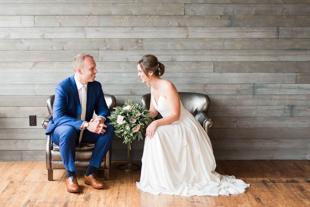 bride_and_groom_sitting_in_arm_chairs_laughing_wood_floors_industrial_venue.jpg