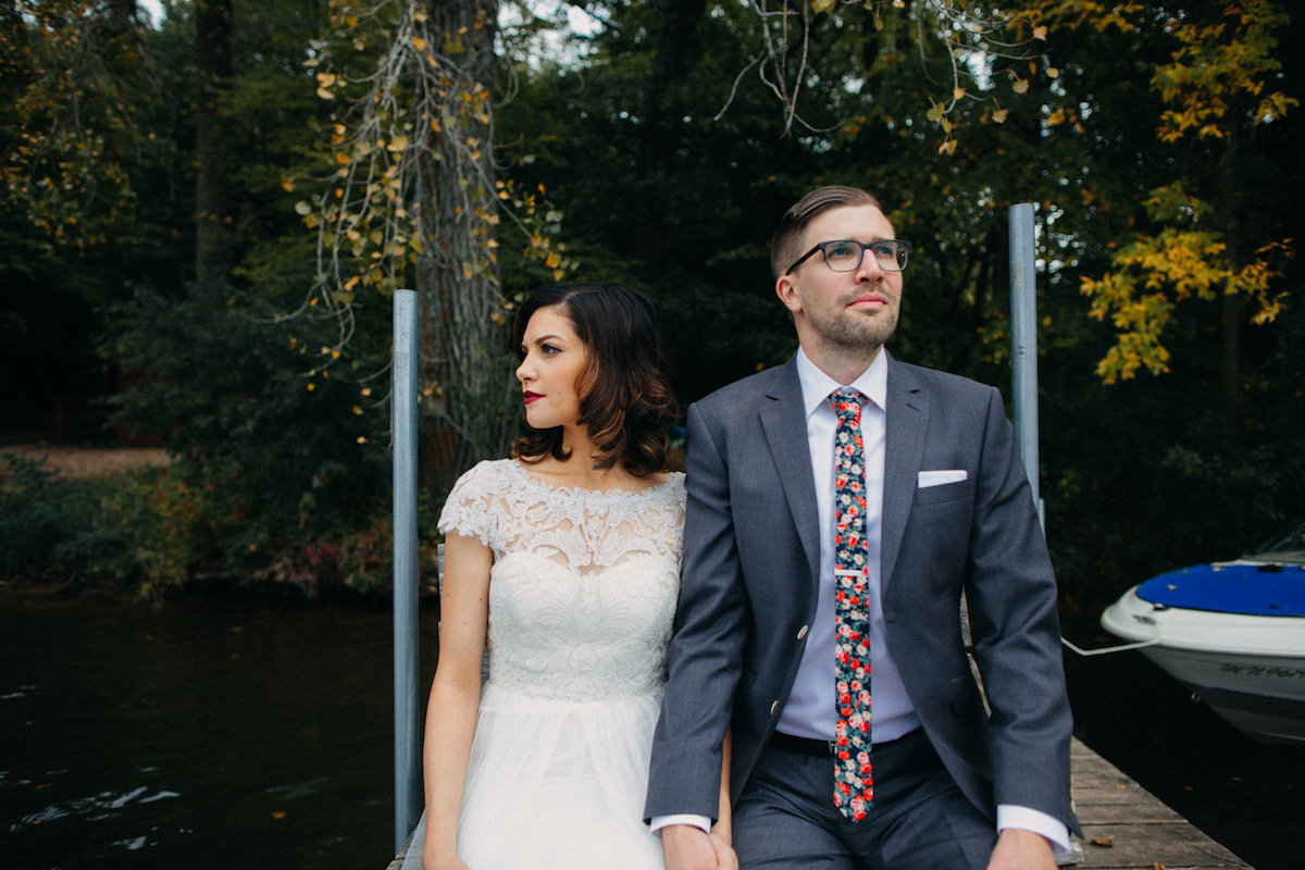 bride_and_groom_sitting_on_wooden_lake_dock_in_autumn_woods.jpg