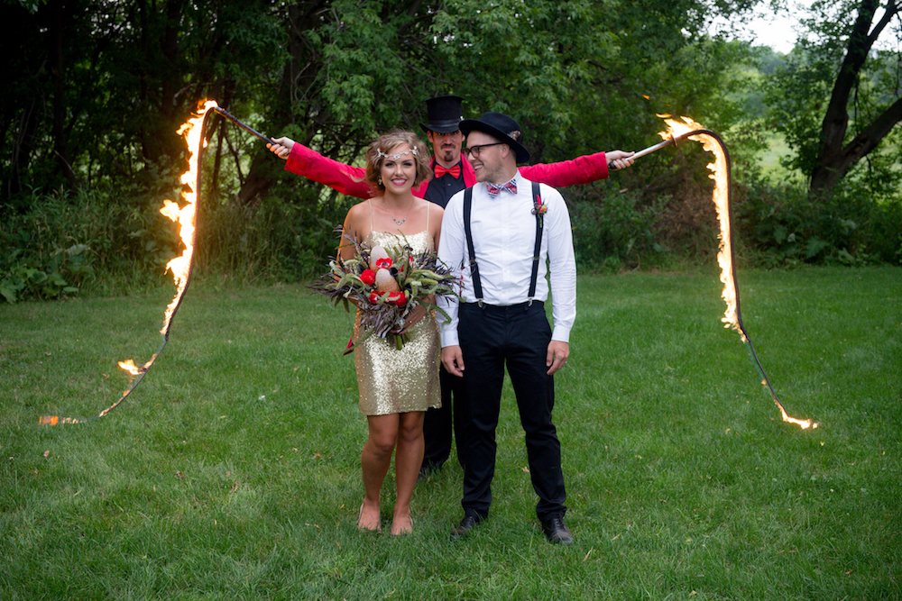 bride_and_groom_smiling_acrobat_with_fire_behind.JPG