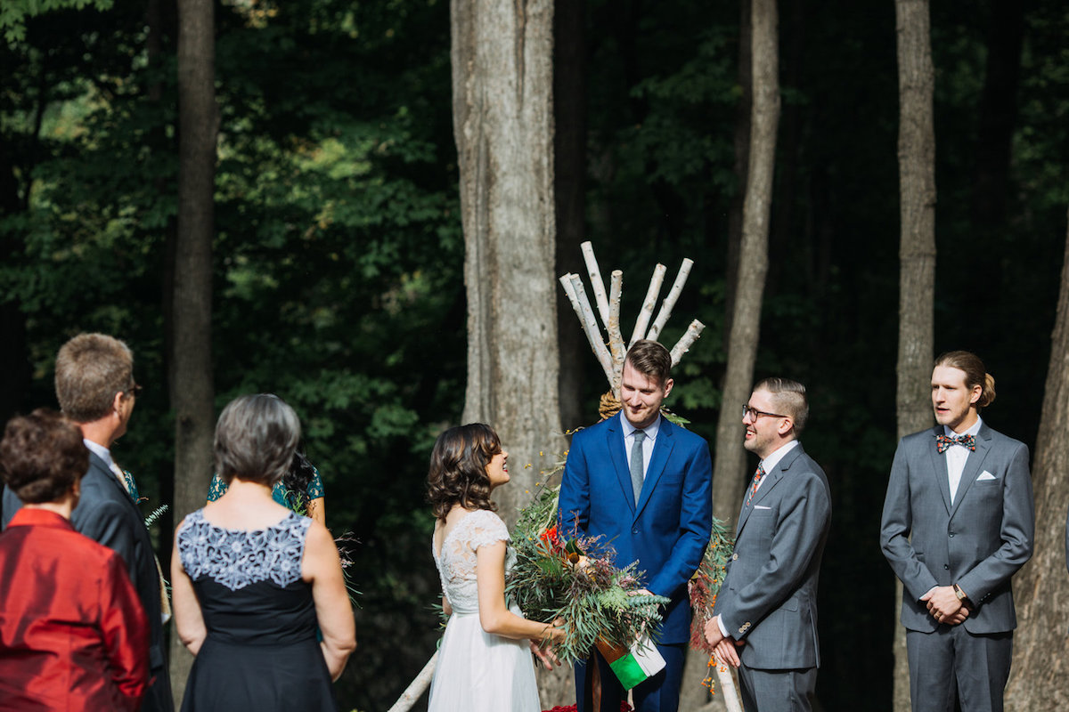 bride_and_groom_smiling_at_each_other_during_woodsy_camp_wedding_ceremony.jpg
