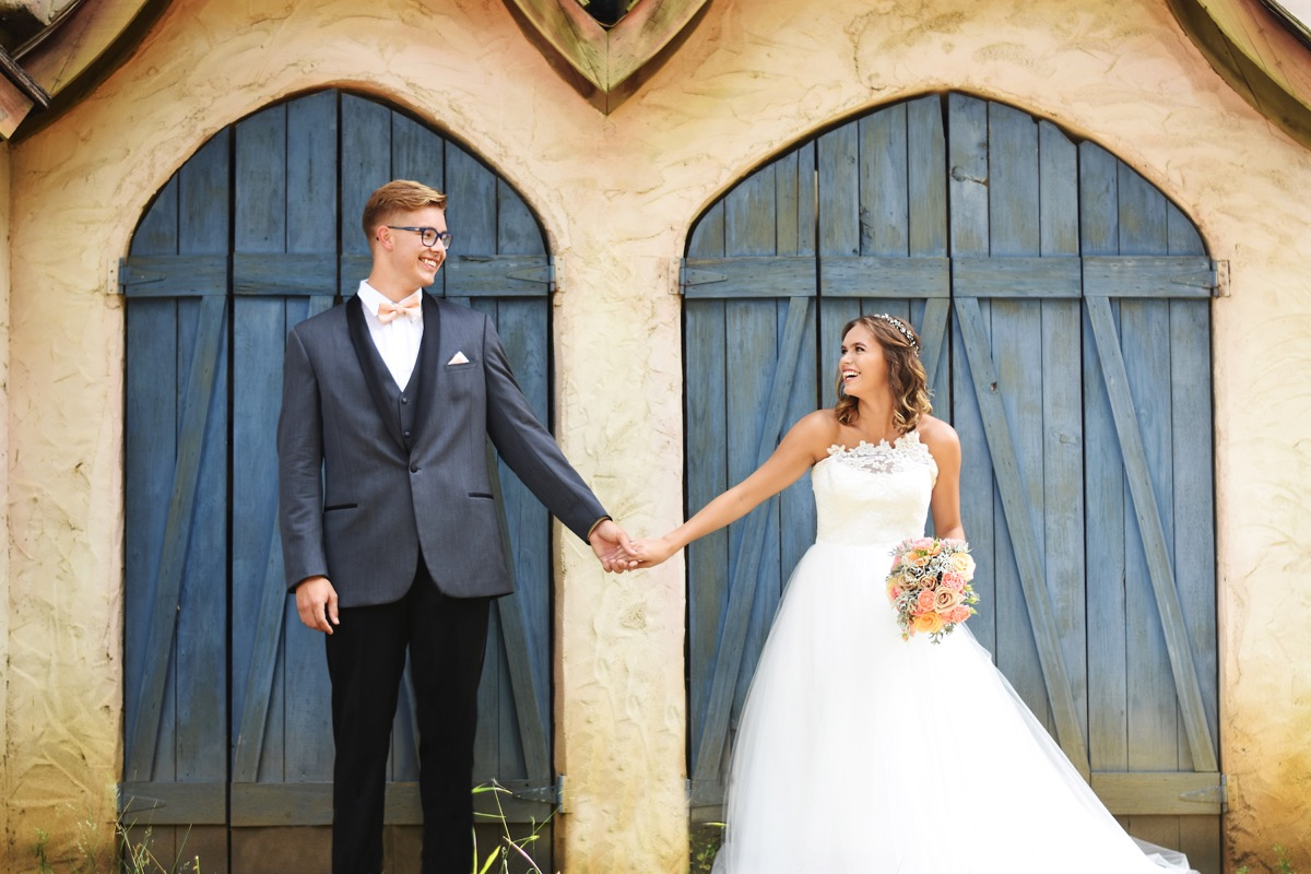 bride_and_groom_standing_apart_holding_hands_blue_doors.jpg