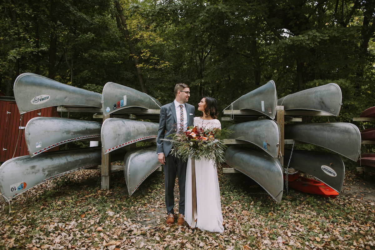 bride_and_groom_standing_by_canoes_in_woods_wedding_camp_inspired.jpg
