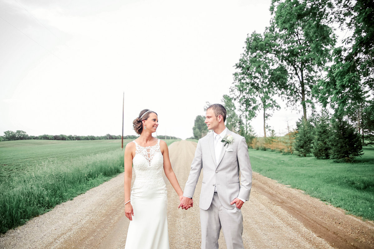 bride_and_groom_standing_on_gravel_road_near_fields_holding_hands_smiling.JPG